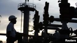 FILE- A technician checks pipelines at Bangchak oil tanks in Bangkok September 7, 2005.