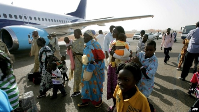 Ethnic South Sudanese board a plane to fly home at Sudan's Khartoum airport, May 14, 2012.