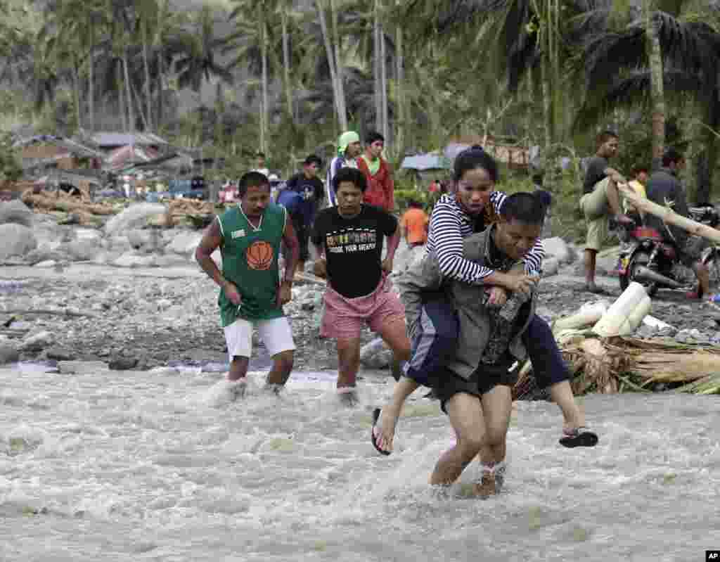 Dân trong làng Andap, tỉnh Compostela Valley tìm cách băng ngang một khu vực gặp lũ quét.