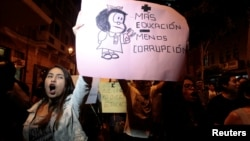 "Protesters hold a sign reading ""More education less corruption"" to protest against a plan by opposition lawmakers to oust Peru's Education Minister Jaime Saavedra in Lima, Peru, Dec. 12, 2016."