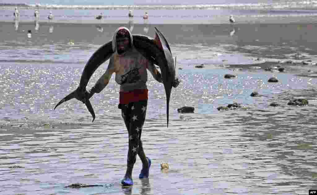 Pescador transporta espadarte para o mercado de Aden, no Iemen.