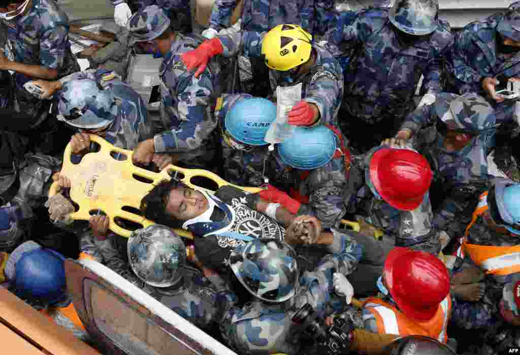 Nepalese police personnel carry earthquake survivor Pemba Tamang (C) on a stretcher after his rescue from a destroyed hotel building in Kathmandu. Rescuers pulled the 15-year-old boy alive from the rubble five days after an earthquake that killed nearly 6,000 people.
