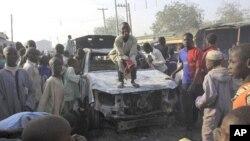 Wani yaro yana tsaye kan motar 'yan sanda aka kona lokacin wani hari kan caji ofis na Sheka a Birnin Kano, 25 Janairu 2012