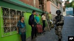 Residentes el barrio Antimano de Caracas, Venezuela, se paran cerca de una pared mientras observan a un miembro de la Fuerza de Acción de la Policía Nacional, o FAES, patrullar por el área . Enero 29, 2020.