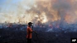 Salah seorang anggota tim pemadam kebakaran berusaha mengatasi kebakaran hutan di Pemulutan, Sumatra Selatan pada Juli 2015 (foto: dok).