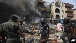 Polisi Nigeria sedang memeriksa lokasi kebakaran pabrik dan rumah di Lagos, Nigeria (26/12). Komisi HAM Nasional Nigeria mengecam dinas polisi rahasia negara itu atas penahanan dua wartawan, Sabtu (29/12).