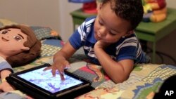 FILE - Frankie Thevenot, 3, plays with an iPad in his bedroom at his home in Metairie, La.