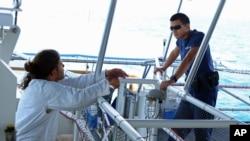 U.S. Coast Guard firemen Eddie Toledano (r) talks to a Cuban migrant on board the USCG Cutter Charles David Jr. in the Florida Straits, May 17, 2015.