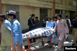 FILE - Hospital workers push a stretcher carrying the body of a policeman who was one of the policemen shot dead in Quetta, Pakistan, July 13, 2017.