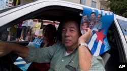A man drives his car holding a poster with pictures of the Cuban Five, celebrating their freedom, in Havana, Cuba, Dec. 17, 2014.