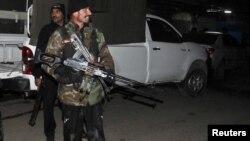 ຕໍາຫລວດຜູ້ນຶ່ງຢືນຍາມ ຢູ່ໃກ້ບ່ອນທີ່ຈະຫລວດຍິງໃສ່ ຢູ່ສະໜາມບິນສາກົນຂອງເມືອງ Peshawar ໃນວັນທີ 15 ທັນວາ 2012 ຊຶ່ງໄດ້ເຮັດໃຫ້ 4 ຄົນເສຍຊີວິດ ໃນໄລຍະທີ່ ພວກທໍາການໂຈມຕີສະລະຊີບສູ້ລົບກັນ ກັບທະຫານເປັນເວລາ 30 ນາທີ. REUTERS/Fayaz Aziz(PAKISTAN - Tags: CIVIL UNREST POLITICS)
