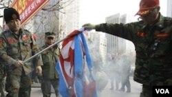 Beberapa eks anggota marinir Korea Selatan membakar bendera Korea Utara dalam unjuk rasa di Seoul, Sabtu.