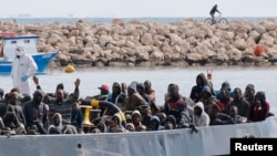 FILE - After more than 300 migrants died Friday trying to cross the Mediterranean, other migrants arrived by boat at the Sicilian harbor of Pozzallo, Italy, Feb.15, 2015.