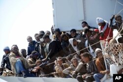 "FILE - Migrants wait to disembark from the Italian Navy vessel ""Chimera"" in the harbor of Salerno, Italy, April 22, 2015."
