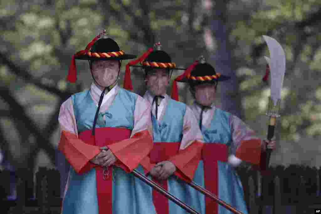 Performers wearing traditional guard uniforms and protective face masks as a precaution against the coronavirus, stand during a re-enactment ceremony of the changing of the Royal Guards, in front of the main gate of the Deoksu Palace in Seoul, South Korea.