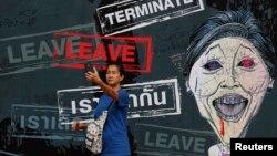 Biểu ngữ với tranh biếm họa Thủ tướng Yingluck Shinawatra tại khu trại của người biểu tình chống chính phủ ở trung tâm Bangkok, ngày 25/2/2014.