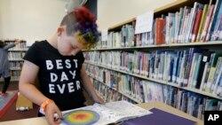 Sam yang berusia 9 tahun sedang membaca buku di perpustakaan Bay Area Rainbow Day Camp di El Cerrito, California, 12 Juli 2017.