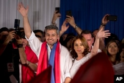 Paraguay's President Elect Mario Abdo Benitez. left, of Colorado Party, and his wife Silvana Lopez Moreira wave at supporters during celebrations at the party headquarter's in Asuncion, April 22, 2018.