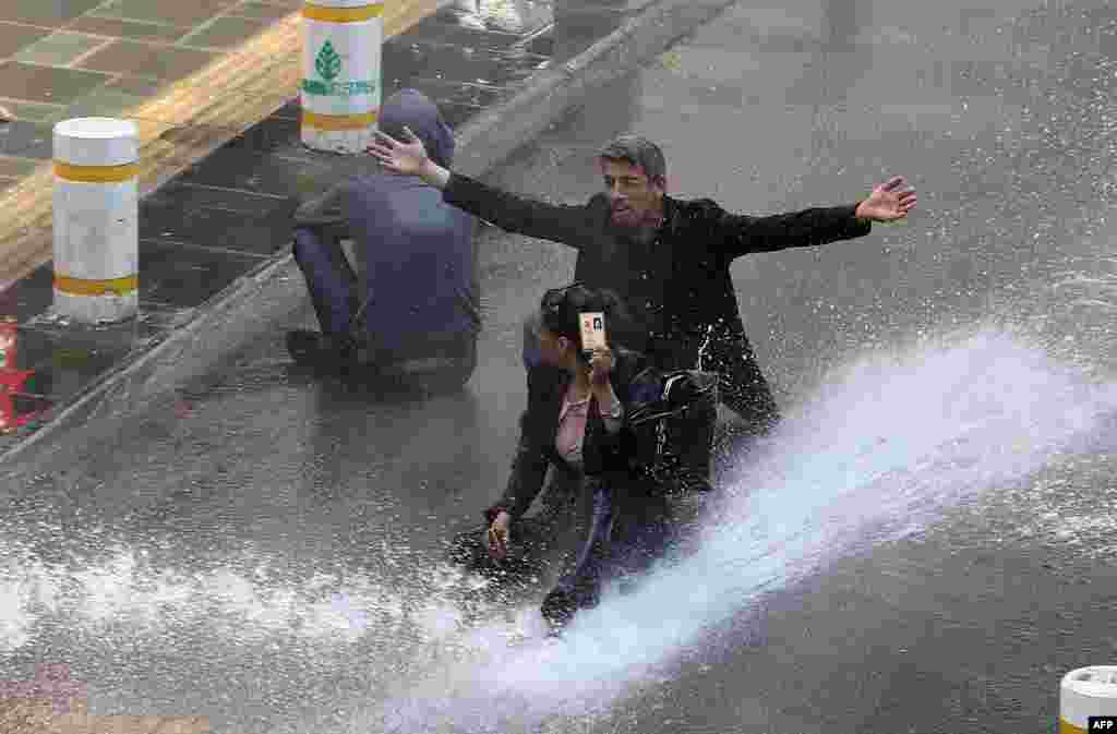 A woman shows her identity card next to another protester as riot police use water cannons during clashes after hundreds of people tried to reach the city's main Kizilay Square to celebrate May Day in Ankara, Turkey.