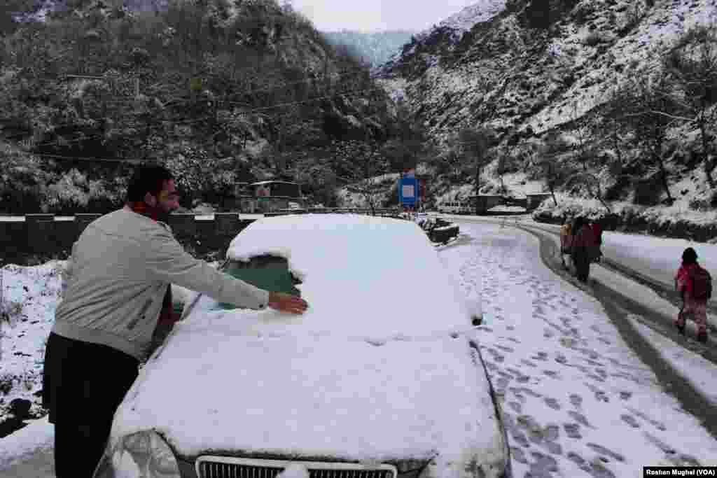 ایک شخص اپنی گاڑی سے برف ہٹاتے ہوئے۔