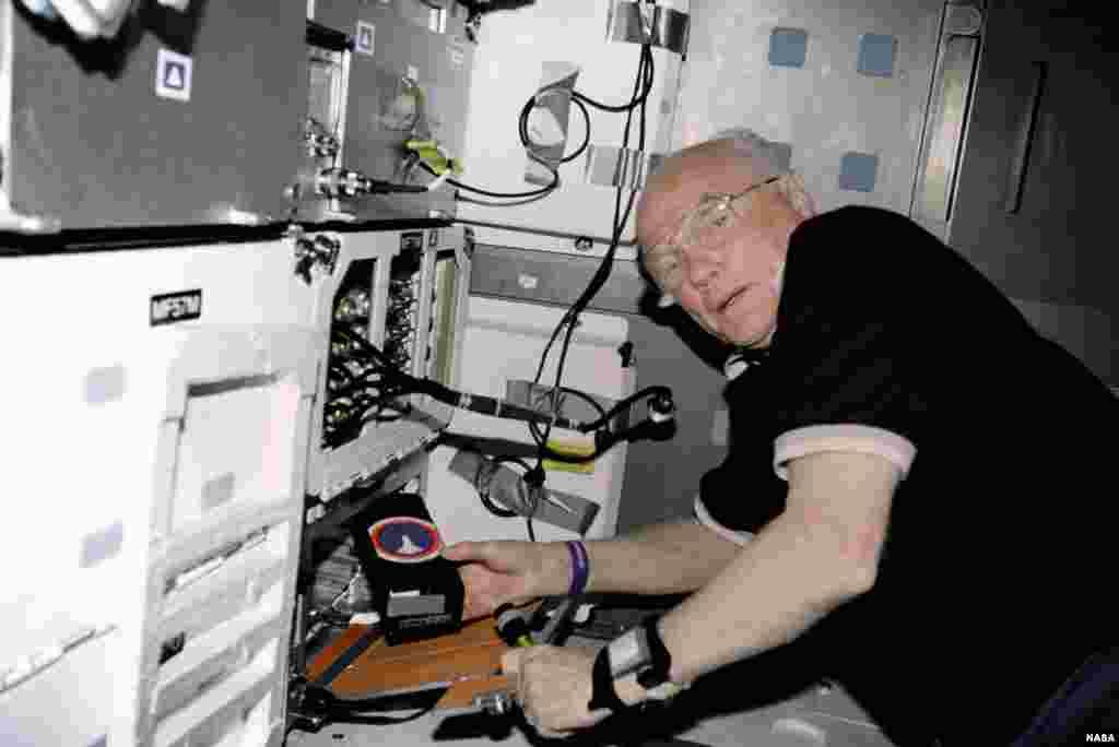 El especialista de carga útil STS-95, John Glenn, trabaja con el Experimento de Osteoporosis en Órbita (OSTEO), ubicado en un armario del Discovery, en noviembre de 1998.