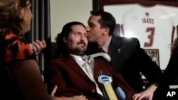 FILE - Former Boston College baseball captain Pete Frates, seen center left in this Dec. 13, 2016 photo, receives a kiss from Boston College head baseball coach Mike Gambino after Frates was presented with the 2017 NCAA Inspiration Award, during ceremonies in Frates home in Beverly, Mass.
