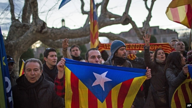 "Pro-independence supporters holds ""estelada"" flags as they celebrate the results of a symbolic declaration of sovereignty in front of Catalonia's Parliament in Barcelona, Spain, Jan. 23, 2013."