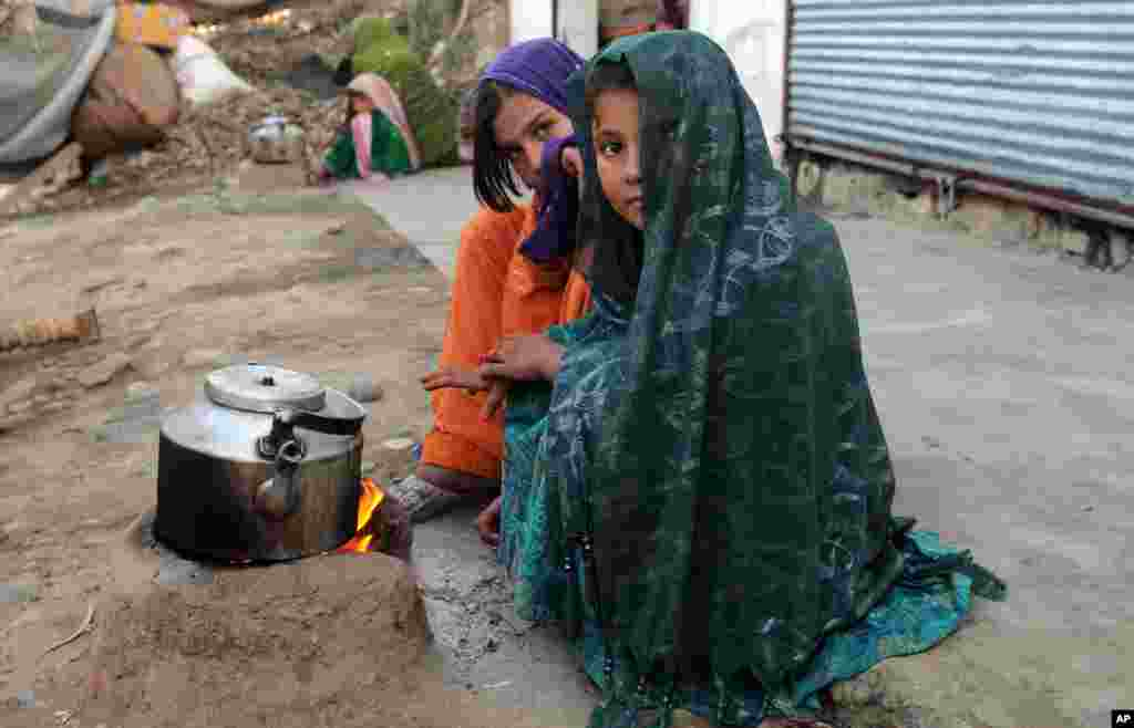 Internally displaced girls warm up by a stove in the Achin district of Afghanistan.