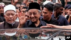 PM Malaysia Mahathir Mohamad (tengah) melambai kepada pendukungnya setelah menunaikan shalat Jumat di Masjid Nasional, Kuala Lumpur, Malaysia (11/5).