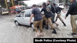 کراچی میں بارش کے پانی سے خراب ہونے والی گاڑی کو پولیس اہلکار دھکا لگا رہے ہیں۔