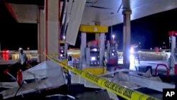 In this image made from video, debris from tornadoes pile around the pumps of a gas station, Oct. 10, 2021, in Shawnee, Oklahoma.