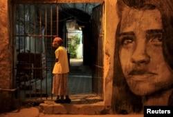 FILE - An elderly woman stands outside her house in Havana, Cuba, Dec. 31, 2015.