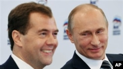Russian President Dmitry Medvedev, left, and Russian Prime Minister Vladimir Putin participate in a video conference with regional offices of the United Russia party, at the party's headquarters, Moscow, October 21, 2011.