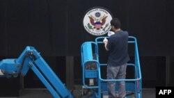 Radnik uklanja znak na ulazu u američki konzulat u Čengduu