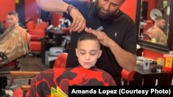 Austin Lopez reads a book to Amir Shalash as he gets his hair cut at Prince Cuts Barbershop, Lexington, KY