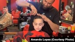 Austin Lopez reads a book to Amir Shalash as he gets his hair cut at Prince Cuts, Lexington, KY