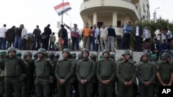埃及军人守护总统府,抗议者在水泥路障上示威