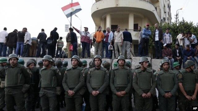 Binh sĩ Ai Cập đứng gác gần dinh tổng thống trong thủ đô Cairo, trong khi những người biểu tình phản đối đứng trên các bục xi măng phía sau 9/12/12