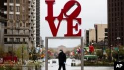 """Një person me maskë ecën në sfondin e një vepre arti me mbishkrimin """"Dashuri"""" në Filadelfia"""