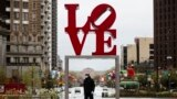 """A person wearing a protective face mask and gloves as a precaution against the coronavirus walks by the Robert Indiana sculpture """"LOVE"""" at John F. Kennedy Plaza, commonly known as Love Park, in Philadelphia, Monday, April 13, 2020. (AP Photo/Matt Rourke)"""