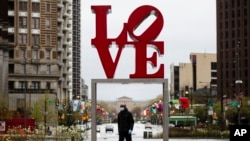 "A person wearing a protective face mask and gloves as a precaution against the coronavirus walks by the Robert Indiana sculpture ""LOVE"" at John F. Kennedy Plaza, commonly known as Love Park, in Philadelphia, Monday, April 13, 2020. (AP Photo/Matt Rourke)"