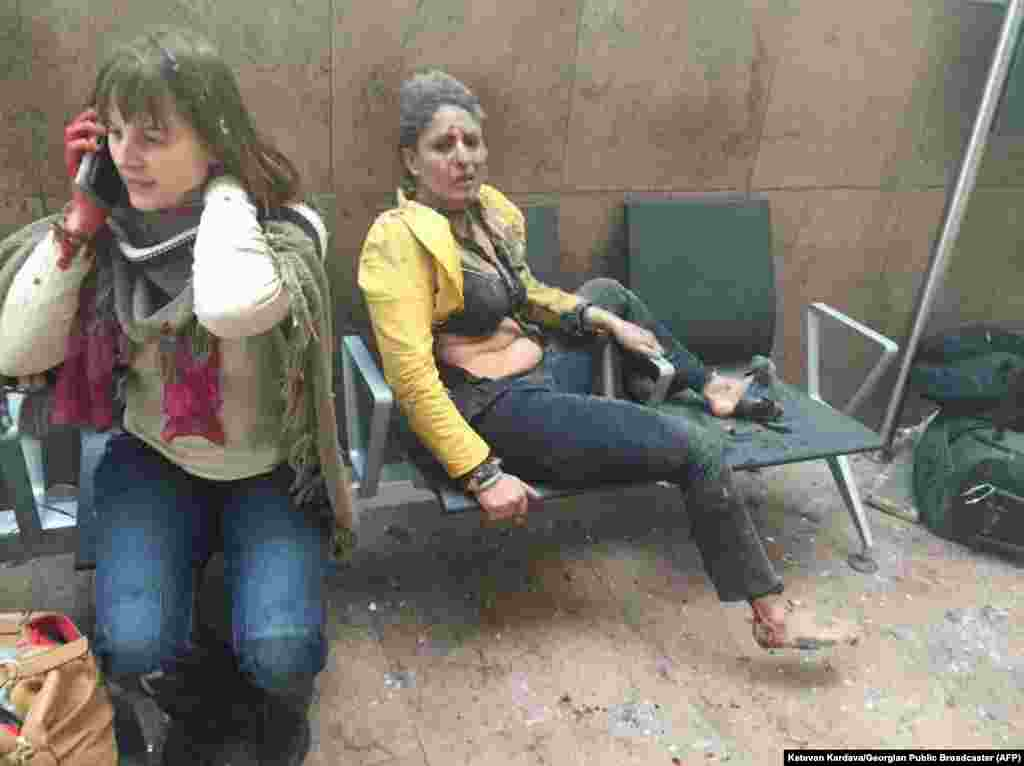 An injured woman looks on as another speaks on her mobile phone following twin blasts at Brussels airport in Zaventem. Airlines cancelled hundreds of flights and European railways froze links with Brussels after a series of bomb blasts killed around 35 people in the city's airport and a metro station, sparking a broad security response.