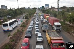 FILE - Drivers sit in queues of traffic on a highway in downtown Nairobi, Kenya, April 14, 2015. Taxi operators want the government to stop operations of ride-sharing app Uber.