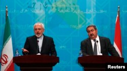 Iranian Foreign Minister Mohammad Javad Zarif, left, speaks during a news conference with Iraqi Foreign Minister Hoshiyar Zebari in Baghdad, Aug. 24, 2014.
