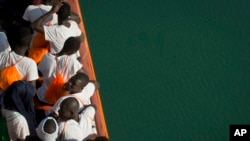 FILE - African migrants who were rescued from the Mediterranean Sea north of the Libyan coast, stand on the deck as the boat approaches the port of Pozzallo in Sicily, Italy, Sept. 1, 2017.