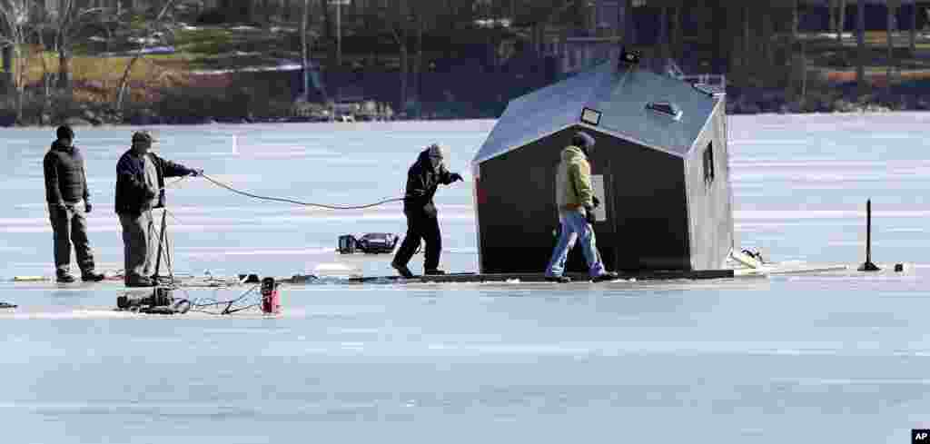 A crew from Gulbicki's towing service works to extract a bob house that broke through the ice on Lake Winnipesaukee in Meredith, New Hampshire, USA. The small shack is used by ice fisherman and broke through the ice over the weekend.