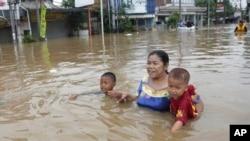 Seorang ibu membawa dua anaknya mengarungi banjir di Jakarta (13/1). (AP/Achmad Ibrahim)