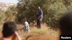 Những người lập cư Do Thái (giữa) mang súng đi quanh cánh đồng ô liu trong mùa thu hoạch ô liu của người Palestine gần một khu định cư phía đông thành phố Nablus, ngày 15 tháng 10, 2010.
