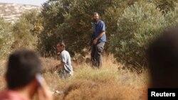 요르단강 서안지구 올리브 나무 조성 지역에 팔레스타인이 주민들이 나타나자 이스라엘인들이 총을 겨누는 모습.