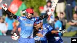 Afghanistan's Hamid Hassan raises his bat in celebration after their Cricket World Cup Pool A win over Scotland in Dunedin, New Zealand, Thursday, Feb. 26, 2015.